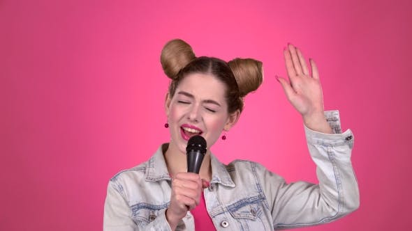 Thumbnail for Teenager Sings Into the Microphone. Pink Background
