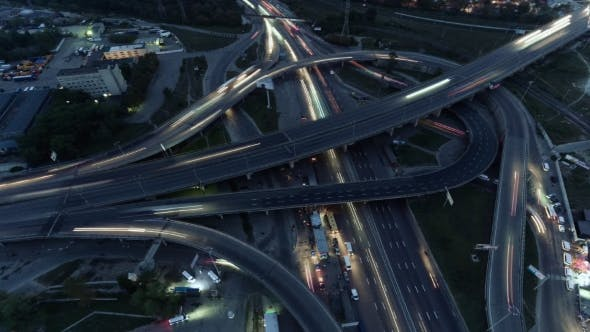 Thumbnail for Overhead Flyover the Complex Road Junction Highway. Night Light, Sunset. High Altitude Drone Flight.
