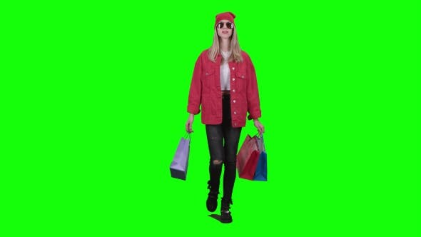 Thumbnail for Teenager in Glasses Goes Shopping, Holding Packages in His Hands. Green Screen