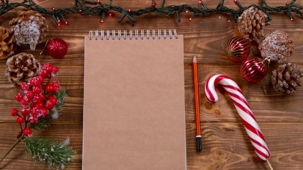 Mockup Notebook and Pencil Lie on the Table, Christmas Toys and Garlands Around. Top View