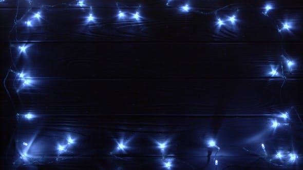 Thumbnail for Christmas Garland Burns Bright Light Lying on a Table in a Dark Room. Top View