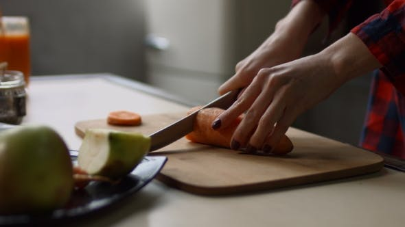Thumbnail for Female Hands Cutting Raw Carrot on Chopping Board