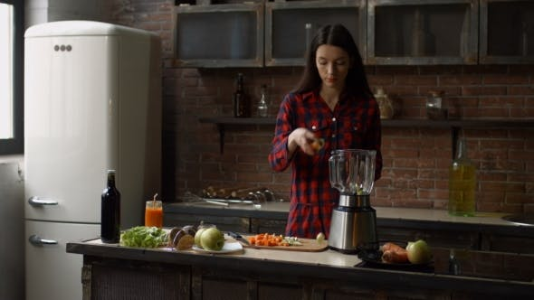 Woman Puts Chopped Food Ingredients Into Blender