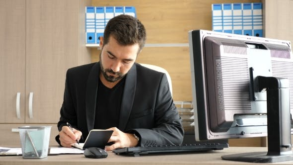 Thumbnail for Young Businessman in His Office Taking Notes in a Paper Notebook