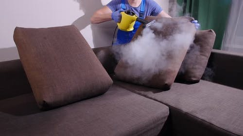 Furniture Cleaning Concept. Cleaning the Sofa with an Antibacterial Steam Cleaner