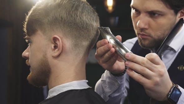 Thumbnail for eines gutaussehenden Professioanl Barber Stylign Haar eines Mannes