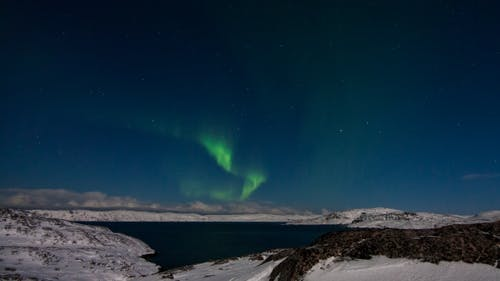 Northern Lights in the Snow-covered Mountains. Norway