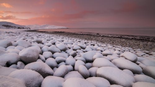 Sunset on the Snow-covered Beach of the Barents Sea