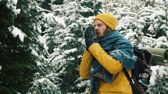 Thumbnail for Man in Yellow Winter Jacket Cleans His Hands From Snow Standing in the Mountain Forest