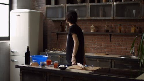 Lovely Woman in Kitchen Following Recipe on Tablet