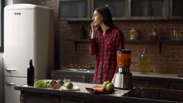 Thumbnail for Junge Frau im Gespräch auf Handy während des Kochens