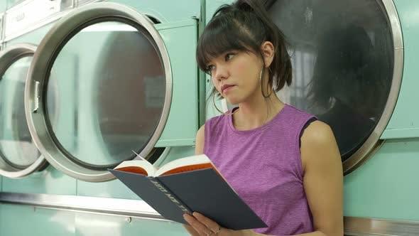Thumbnail for Eine junge Frau sitzt beim Lesen eines Buches, während sie auf ihre Wäsche wartet