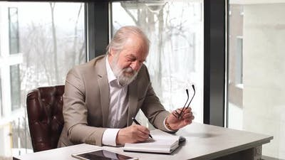 Old Professor with Grey Hair and Beard in Beautiful Suit Taking Notes in the Notebook.