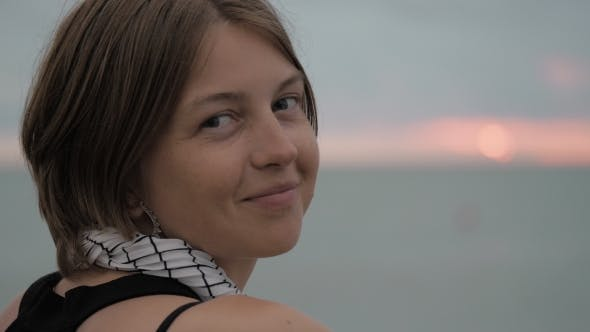 Pretty Girl Smiles at Sunset By the Sea