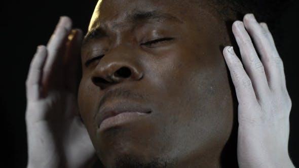 Thumbnail for Weiße Hände des Mädchens bedecken die Ohren eines schwarzen Mannes und er nickt seinen Kopf, als ob Musik hören