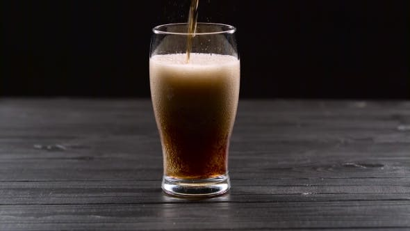 Thumbnail for Cola Is Pouring Into Glass on Black Background
