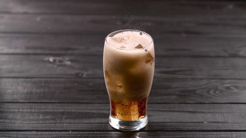 Coca Cola Pouring Into Glass with Ice