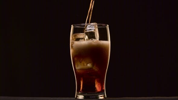 Thumbnail for Cola Poured Into a Glass with Ice It Foams To Form a Foam Cap. Black Background