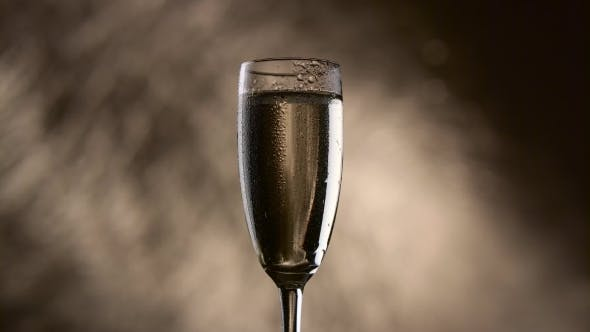 Thumbnail for Drop Drips Down the Wall of a Glass with Champagne on a Bokeh Background
