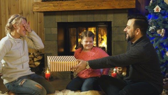 Thumbnail for Junge Familie geben einander Weihnachtsgeschenke