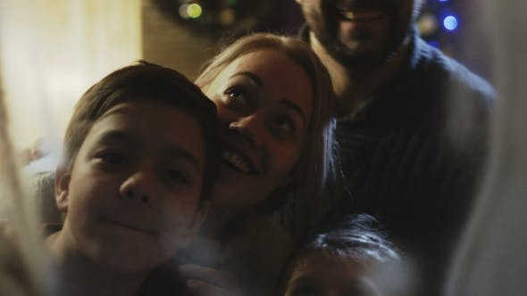 Thumbnail for Cheerful Family Looking Through Window in Christmas Night