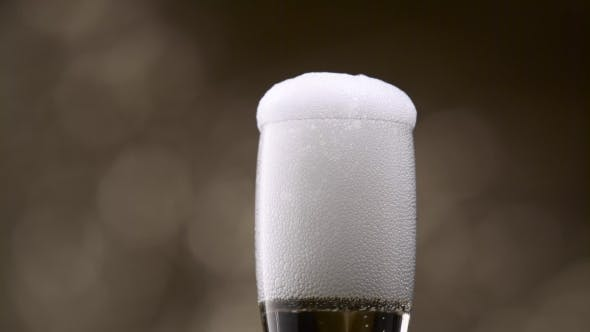 Thumbnail for Champagne Poured Into Glass From Green Bottle. Bokeh Background.
