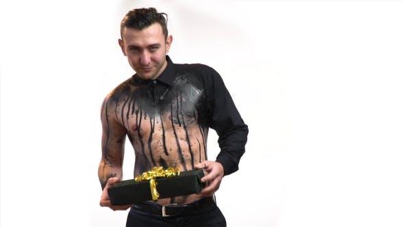 Thumbnail for Niedlicher muskulöser Mann in schwarzer Körperkunst wirft ein Geschenk in seine Hände