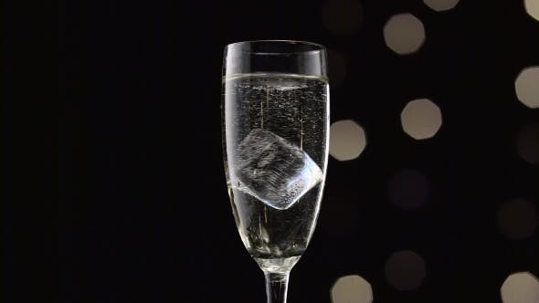 Thumbnail for Cube of Ice Swirls in a Glass of Champagne