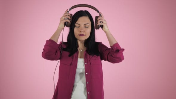 Thumbnail for Beautiful Young Brunette Woman in Headphones Listening To Music and Singing on Color Background