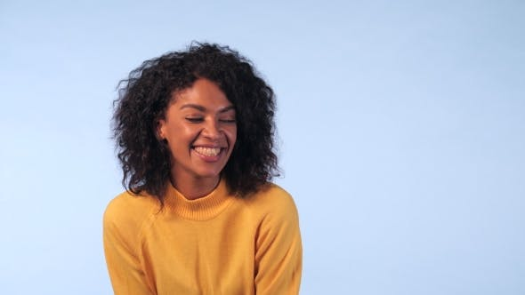 Thumbnail for Cute African Girl in Yellow Sweater on Blue Background in the Studio. The Woman Laughs Sincerely