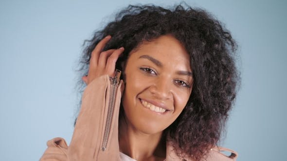 Young African Brazilian Woman Portrait Posing Over Light Blue Background. Trendy and Urban Style