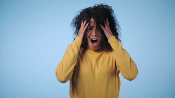 Thumbnail for of a Young African American Stressed Afro Girl Shouting Isolated Over Blue Background. . Stressed