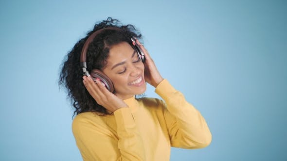 Thumbnail for Mulatto Woman Listening To Music on Colorful Blue Background. Mix Race Girl with Afro Curly Hair in