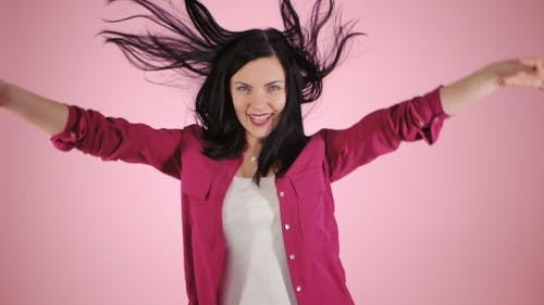 Energy Girl on Pink Background in Studio. She Wears Colorful Shirt. Black Hair in Tail Is Flying