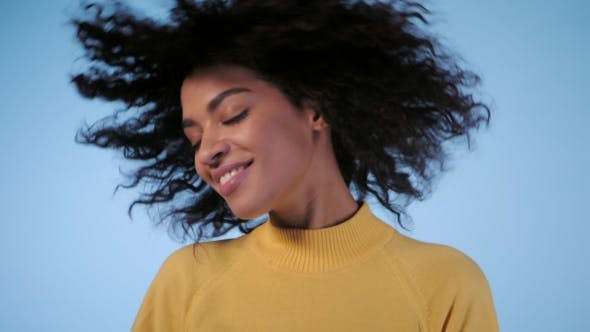 Thumbnail for Beautiful Black Woman with Afro Hair Having Fun Smiling and Dancing in Studio Against Blue