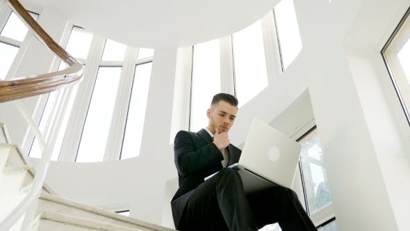 Young Businessman Is Working on the Stairs of Office Buidling next to Big Windows