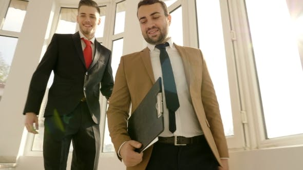 Thumbnail for Two Successful Businessmen Going on the Stairs of an Office Building Talking with Each Other