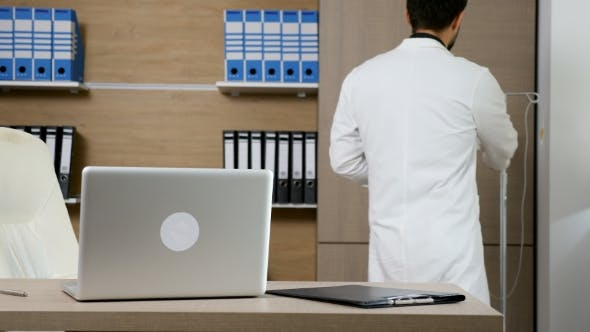 Cover Image for Doctor in His Office at the Laptop