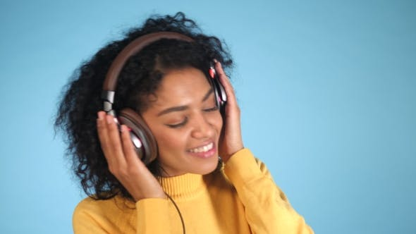 Thumbnail for Smiling Fashion Model with Headphones Posing and Dancing Against Blue Background in Studio