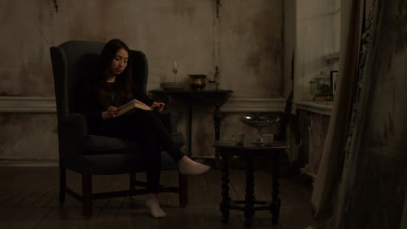 Cover Image for Cute Asian Woman Reading a Book in Retro Interior