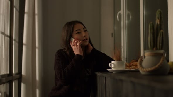 Thumbnail for Gorgeous Asian Girl Talking on Smart Phone at Home