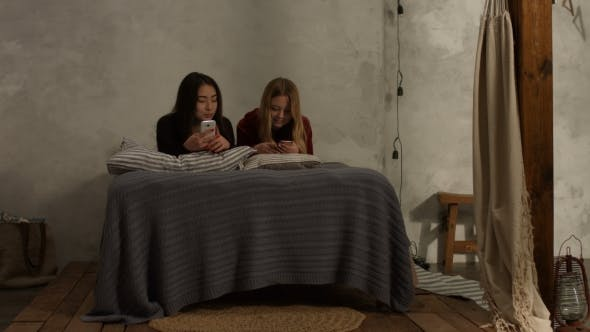 Thumbnail for Diverse Girls Lying on Bed Texting on Phones