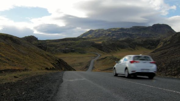 Thumbnail for White Car Is Moving over Road Between Picturesque Icelandic Mountains in Cloudy Weather