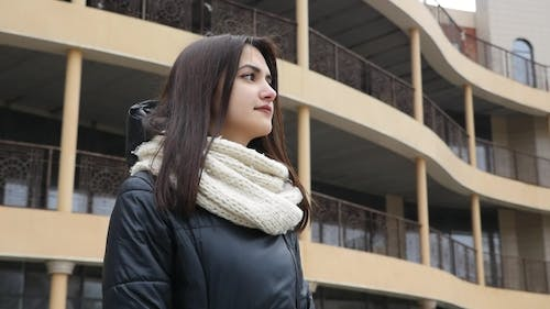 A Stylish Girl Stands Close To a House in a City Street in Winter
