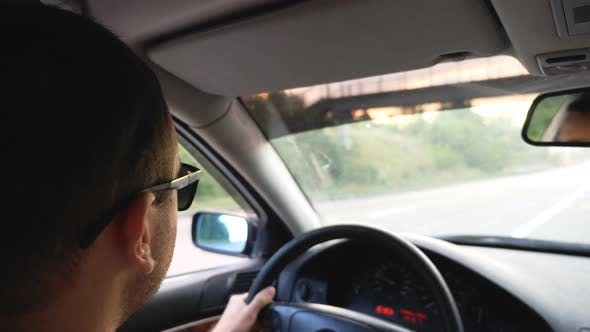 Unrecognizable Man in Sunglasses Driving Car on Highway