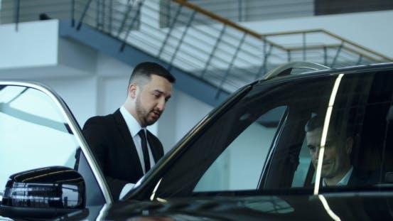 Salesman Presenting Car in Showroom