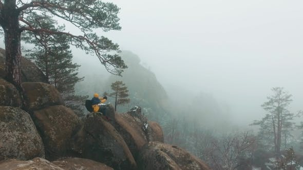 Thumbnail for Air View at the Man Sitting on the Top of the Rock in Winter Mountains Covered with Fog