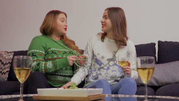Cover Image for Young Girl Talks with Her Fat Girlfriend Sitting at Sofa at Home