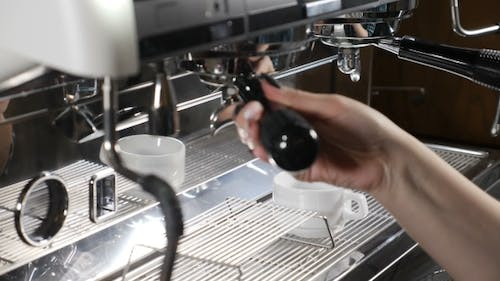 Coffee House.  Pouring Water Out of Automatic Coffee Maker Machine. Coffee Preparing Concept.
