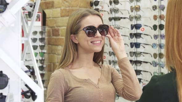 Thumbnail for Happy Young Beautiful Woman Trying on Sunglasses at the Optics Store